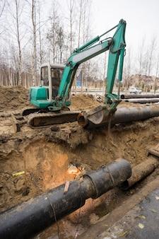 Vervanging van oude leidingen door nieuwe, de lasser werkt in de uitgegraven put.