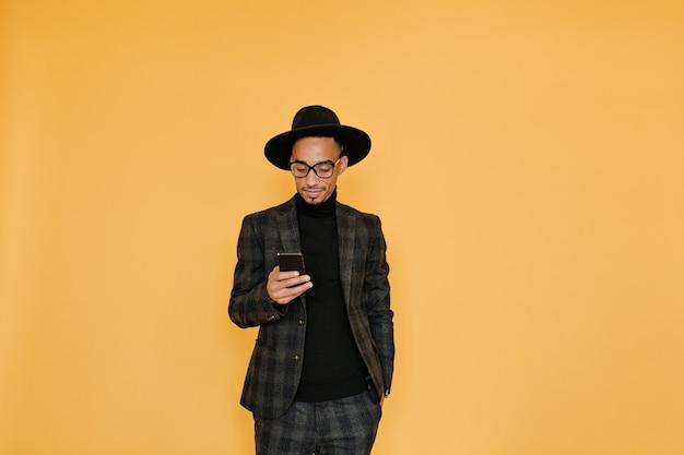 Verveeld afrikaanse man in modieus kostuum staande op gele muur met telefoon. indoor portret van vrolijke zwarte jongen draagt grijze kleding.