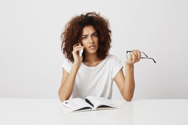 Verveeld afrikaanse meisje praten over telefoon zittend aan tafel over witte muur. kopieer ruimte.