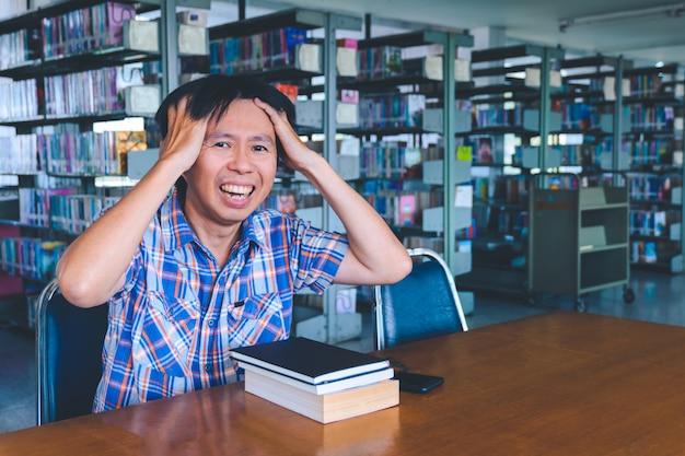 Verveeld aziatische student met boeken in de bibliotheek