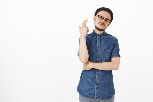 Verveeld beu knappe stijlvolle man met snor en baard in zwarte muts hoofd kantelen weg van vinger pistool gebaar opgeheven in de buurt van hoofd alsof waait geest of schieten uit verveling
