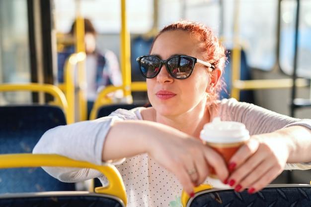 Verveeld blanke vrouw van middelbare leeftijd zitten in de stadsbus, leunend op de stoel en het drinken van koffie te gaan.