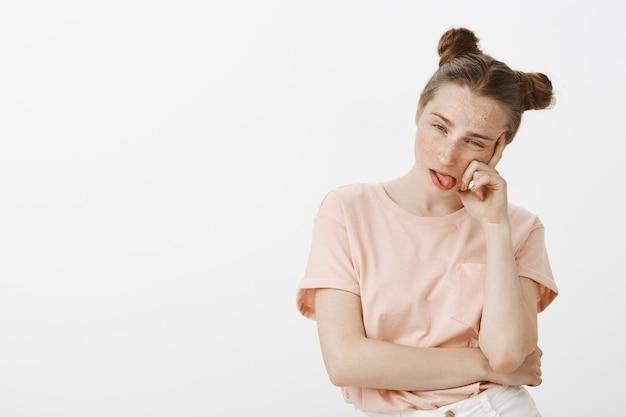 Verveeld en onwillig tienermeisje poseren tegen de witte muur