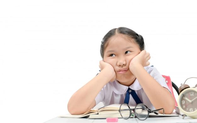 Verveeld en vermoeid meisje dat thuiswerk doet