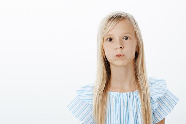 Verveeld en zorgeloos meisje dat probeert op te vrolijken, gek rond. portret van speels schattig jong vrouwelijk kind met blond haar, mokkend, adem inhouden en starend met gepofte ogen