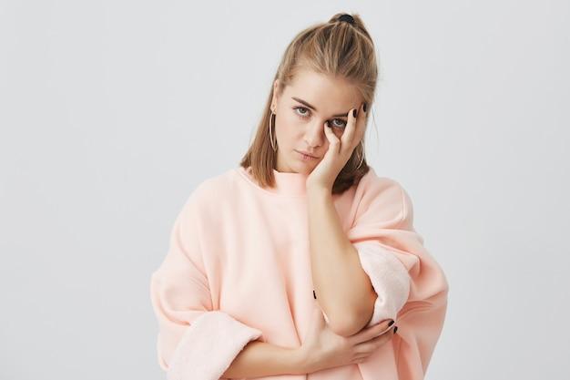 Verveeld europese studente draagt een stijlvol roze sweatshirt dat haar gezicht met de hand aanraakt, er geïrriteerd uitziet, moe van het luisteren naar oninteressante verhalen. lichaamstaal