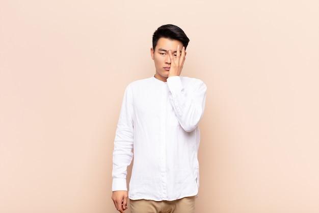 Verveeld, gefrustreerd en slaperig na een vermoeiende, saaie en vervelende taak, gezicht vasthoudend met de hand