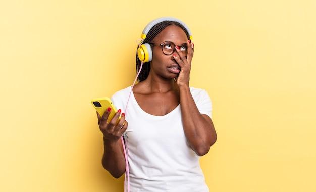 Verveeld, gefrustreerd en slaperig voelen na een vermoeiende, saaie en vervelende taak, gezicht met de hand vasthouden en muziek luisteren