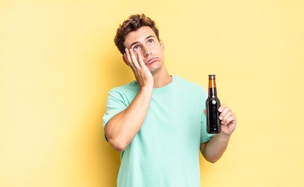 Verveeld, gefrustreerd en slaperig voelen na een vermoeiende, saaie en vervelende taak, het gezicht met de hand vasthouden. bierfles concept