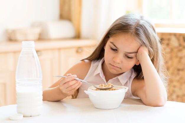 Verveeld jong meisje granen eten voor het ontbijt