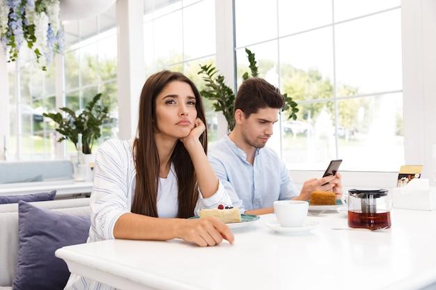 Verveeld jong meisje, zittend aan de tafel van het café terwijl haar vriendje met behulp van mobiele telefoon