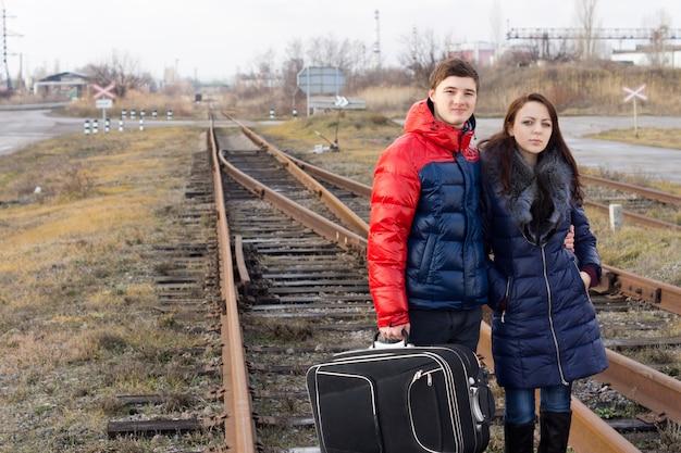 Verveeld jong stel wacht op een trein die arm in arm midden op het spoor staat met hun koffer