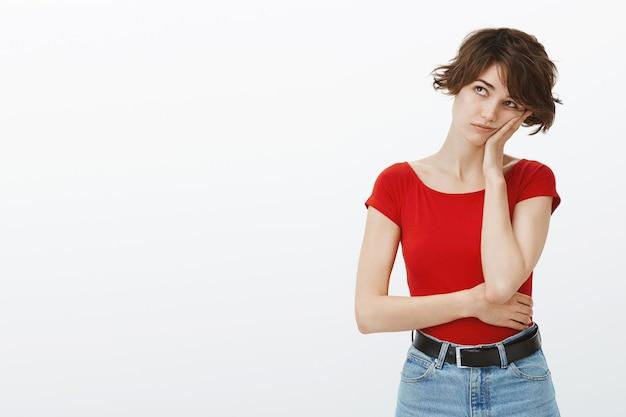 Verveeld jonge vrouw op zoek linkerbovenhoek met onwillig gezicht