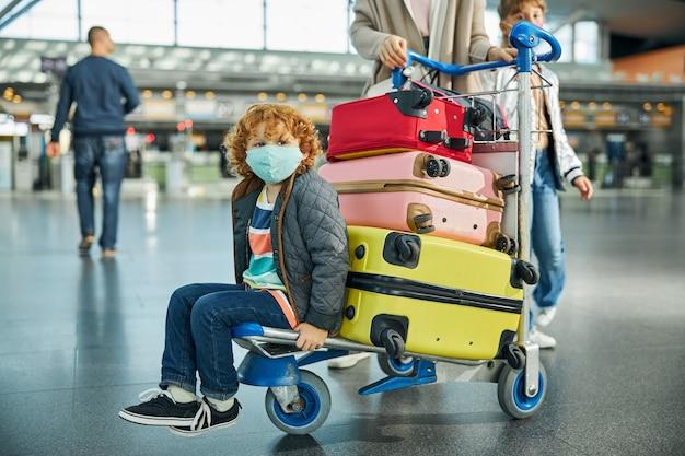 Verveeld kind dat rondkijkt in de luchthaventerminal