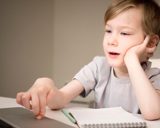 Verveeld kind luisteren naar online lessen