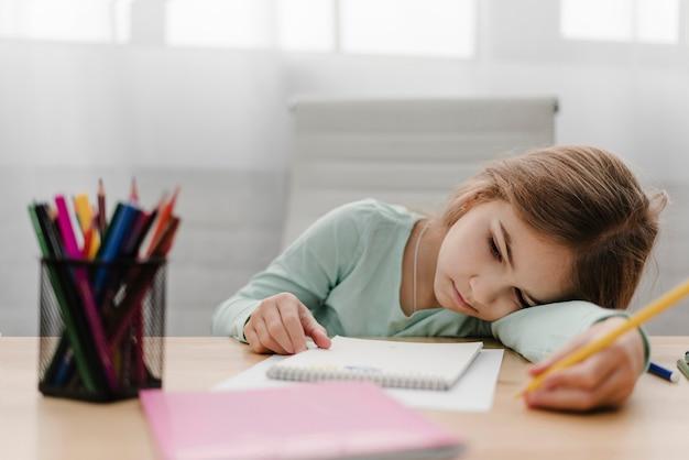 Verveeld klein meisje dat aantekeningen maakt tijdens een online les