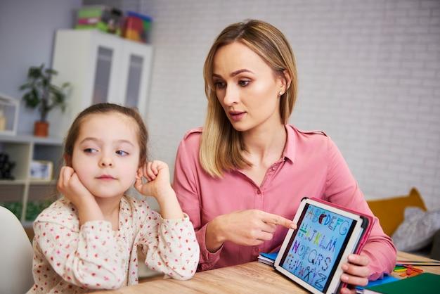 Verveeld meisje en haar moeder studeren met laptop thuis