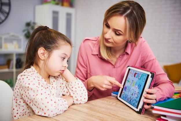 Verveeld meisje en haar moeder studeren thuis met technologie