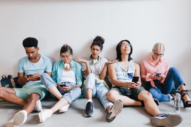 Verveeld meisje met zwart krullend haar boos omdat haar studievrienden niet naar haar luisteren. vermoeide internationale studenten die op de grond zitten en hun telefoons gebruiken na de les.