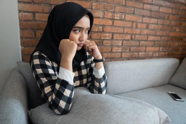 Verveeld moslimvrouw zittend op een bank