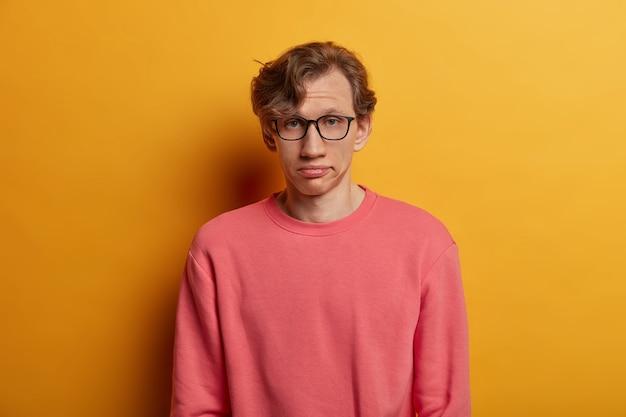 Verveeld, niet onder de indruk mannelijke student kijkt serieus, heeft een uitdrukking van vermoeidheid, draagt een optische bril en een roze trui, zucht van vermoeidheid, geïsoleerd op gele muur. gezichtsuitdrukkingen