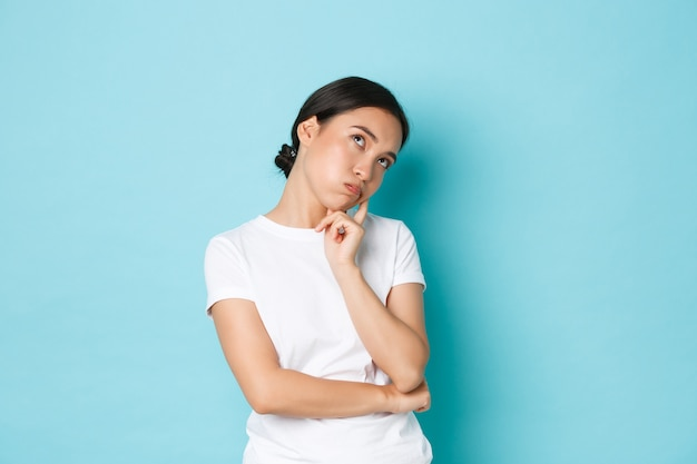 Verveeld of geïrriteerd schattig aziatisch meisje in witte t-shirt met rologen, leun op de handpalm en onverschillig, niet in de stemming, verveling en apathie gevoel, staande blauwe achtergrond niet bezorgd.