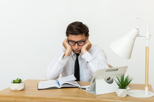 Verveeld op het werk concept, moe ongemotiveerde mannelijke werknemer tijd te verspillen op de werkplek