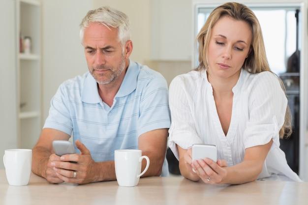 Verveeld paar dat bij het tegen sms'en zit