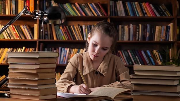 Verveeld schoolmeisje kijkt in boek en schrijft in schrift
