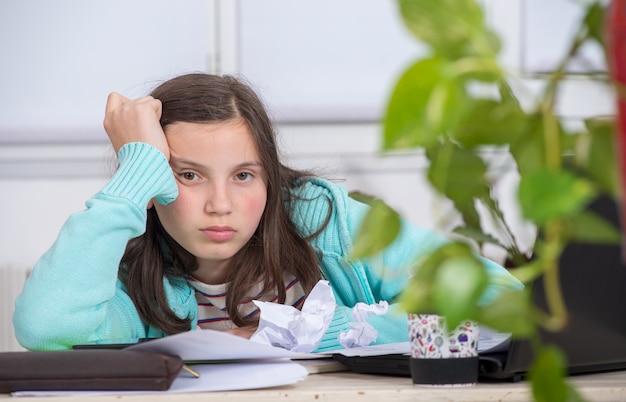 Verveeld tienermeisje doet haar huiswerk