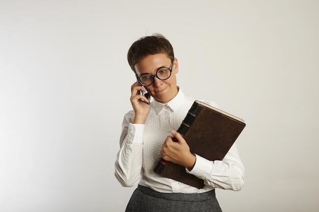 Verveeld uitziende vrouwelijke leraar luistert geduldig naar haar mobiele telefoon geïsoleerd op wit