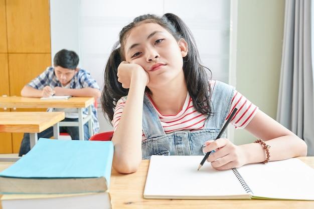 Verveeld vietnamees schoolmeisje zittend aan een bureau in de klas en schrijven in voorbeeldenboek