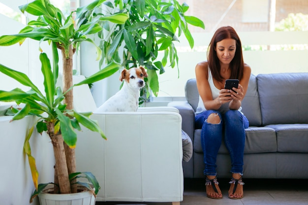 Verveeld vrouw met haar telefoon en hond in de dokter