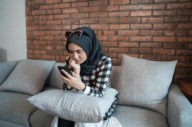 Verveeld vrouw thuis met behulp van haar mobiele telefoon