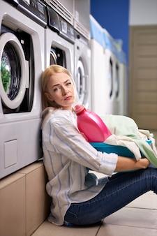 Verveeld vrouw zitten door wasmachine, wachtend op einde wassen, blonde blanke dame met bekken of mand met resterende kleren om te wassen en roze wasmiddel fles