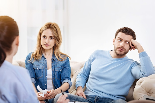 Verveeld zijn. aangename, aardige man met een baard die naast zijn vrouw zit en wegkijkt terwijl hij niet bereid is om deel te nemen aan de discussie