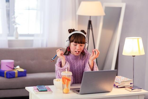 Verveeld zijn. attente brunette weinig vrouw luisteren naar muziek tijdens een pauze
