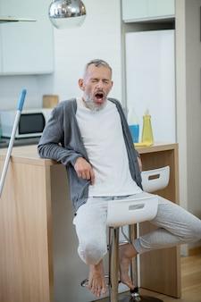 Verveeld zijn. man in huiskleding rust na het schoonmaken van het huis en verveelt zich