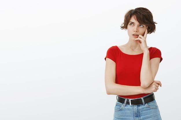 Verveelde en ontevreden vrouw rolt met haar ogen en voelt zich ergens terughoudend over