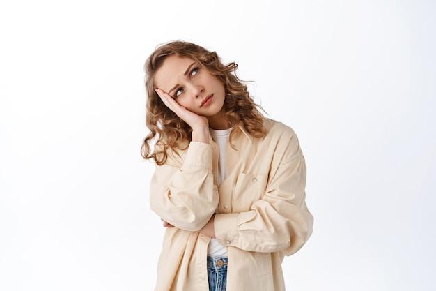 Verveelde en verdrietige vrouw leunt op de hand, kijkt omhoog naar kopieerruimte met een onverschillig gezicht, staande in stijlvolle kleding tegen een witte muur
