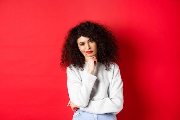 Verveelde en vermoeide gekrulde vrouw met rode lippen die naar de camera kijkt die tegen de achtergrond van de studio staat