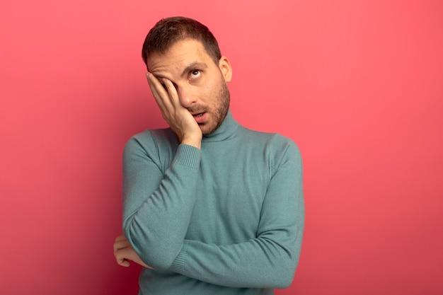 Verveelde jonge blanke man hand op gezicht zetten geïsoleerd op karmozijnrode muur met kopie ruimte opzoeken