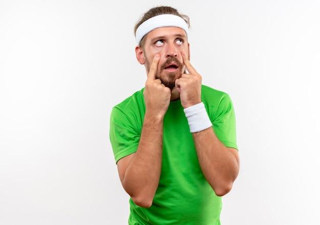 Verveelde jonge knappe sportieve man met hoofdband en polsbandjes die zijn oogleden trekken en omhoog kijken doen verveeld gebaar geïsoleerd op een witte muur met kopieerruimte