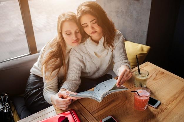 Verveelde jonge vrouwen zitten aan tafel en kijken in het dagboek. ze zijn tevreden. modellen trekken droevige gezichten. blond model zit achter brunette.