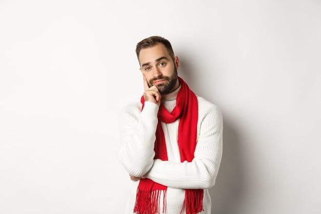Verveelde jongeman die onverschillig en moe naar de camera kijkt, iemand luistert, in de wintertrui en sjaal staat, witte achtergrond