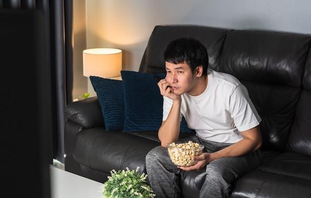 Verveelde jongeman die 's nachts tv kijkt op de bank