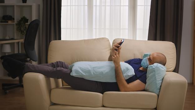 Verveelde man met beschermingsmasker die op de bank ligt te browsen op smartphone tijdens zelfisolatie van het coronavirus.