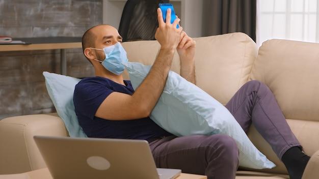 Verveelde man met beschermingsmasker tijdens covid-19 browsen op sociale media met behulp van smartphone.