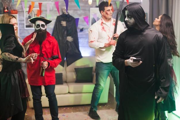 Verveelde man verkleed als een magere hein op halloween-feest met zijn telefoon.
