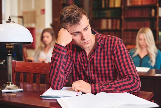 Verveelde mannelijke student tijdens het studeren